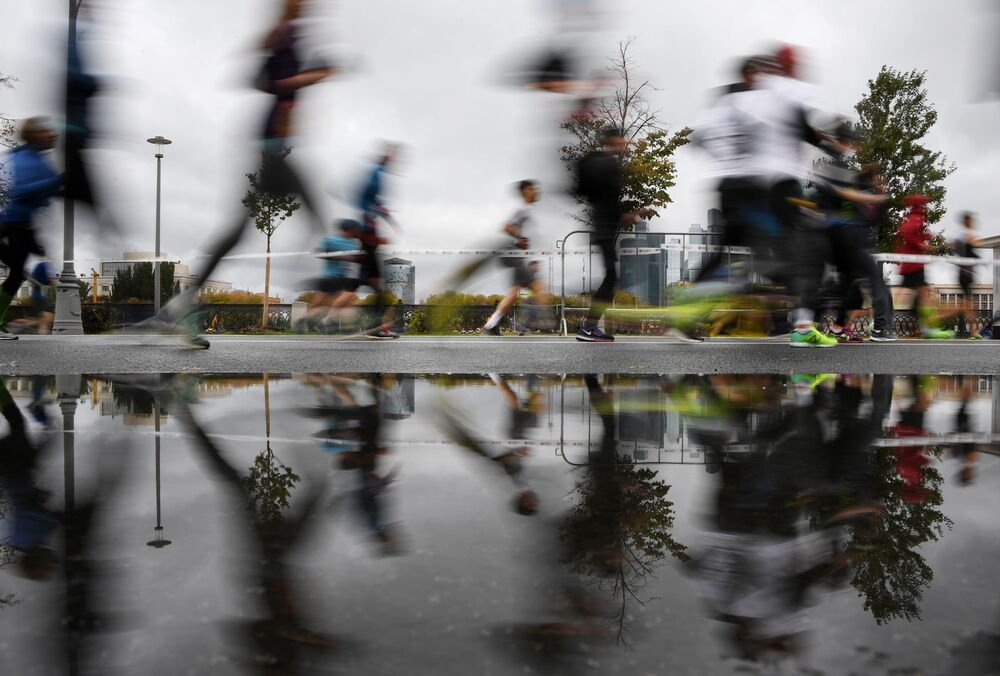 Marathon participants reflect in a puddle as they run during a race in Moscow, Russia.
