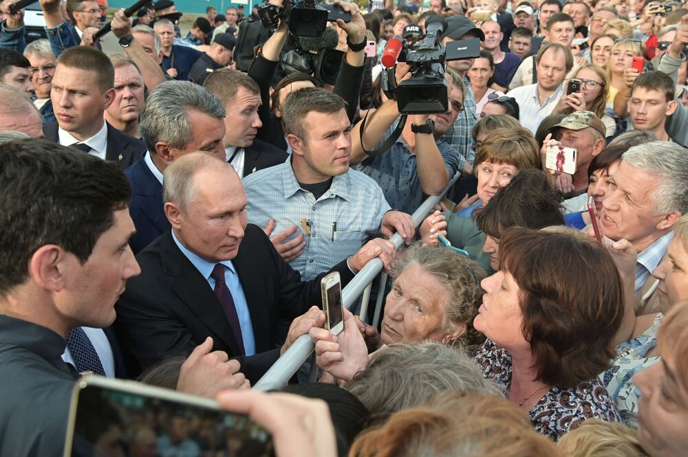 Russia's President Vladimir Putin talks to locals after visiting a school in the town of Tulun in eastern Siberia.