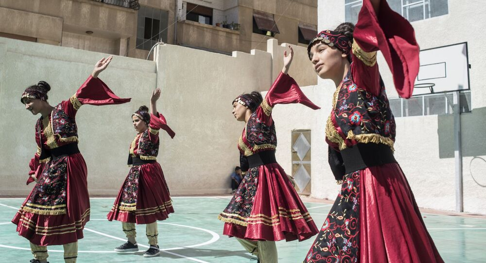 Girls in national costumes perform during the opening of a school in Barzeh district in Damascus