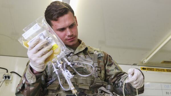 Pfc. Jaritt Louthan, a medical lab technician with 432nd Blood Support Detachment, 28th Combat Support Hospital, 44th Medical Brigade, and a native of Cleveland, re-hydrates freeze dried plasma during an airdrop test Sept. 19, 2019 at Fort Bragg, N.C. Jaritt is among the first few Soldiers to test the durability of the plasma packaging by parachuting to collect data for possible future use on the battlefield - Sputnik International