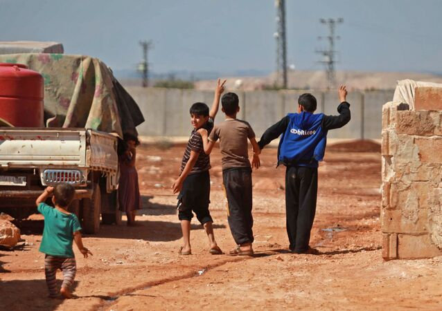 Children gesture towards the barbed-wire-topped concrete fence demarcating the border between Syria and Turkey, at a camp for displaced Syrians in Atme in the northwestern Idlib province, near the borther with Turkey, on September 23, 2019.
