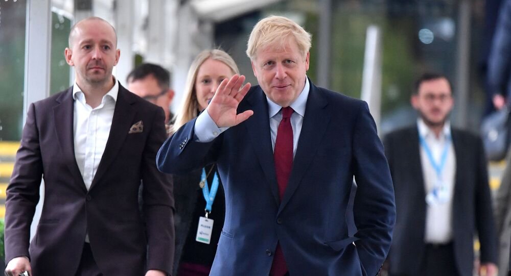 Britain's Prime Minister Boris Johnson (C) returns to his hotel after giving media interviews ahead of the third day of the annual Conservative Party conference in Manchester, north-west England on October 1, 2019.