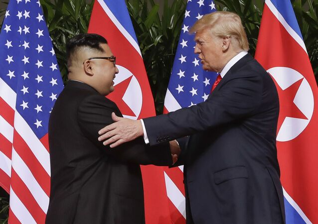 In this June 12, 2018 file photo, U.S. President Donald Trump, right, shakes hands with North Korea leader Kim Jong Un at the Capella resort on Sentosa Island in Singapore. Kim's fifth meeting with Chinese President Xi Jinping continues his ambitious diplomatic outreach that has included summits with the leaders of the United States, South Korea and Russia in the past year and a half. Experts say Kim is attempting to form a united front with North Korea's main ally China to strengthen his leverage in the stalled nuclear negotiations with the United States.