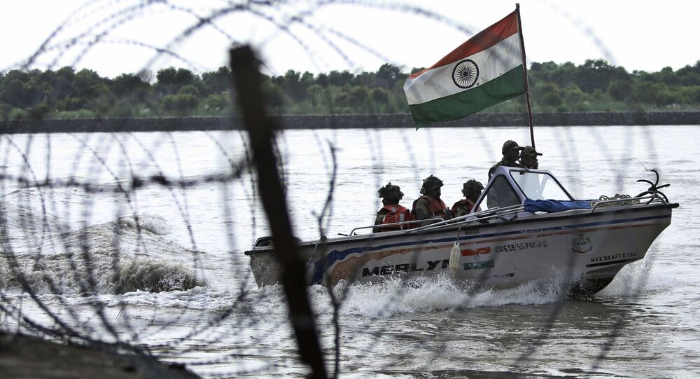 In this Tuesday, Aug. 13, 2019 file photo, Indian Border Security Force (BSF) soldiers patrol on a boat in river Chenab at Pargwal area along the India-Pakistan border in Akhnoor, about 55 kilometers (34 miles) west of Jammu, India