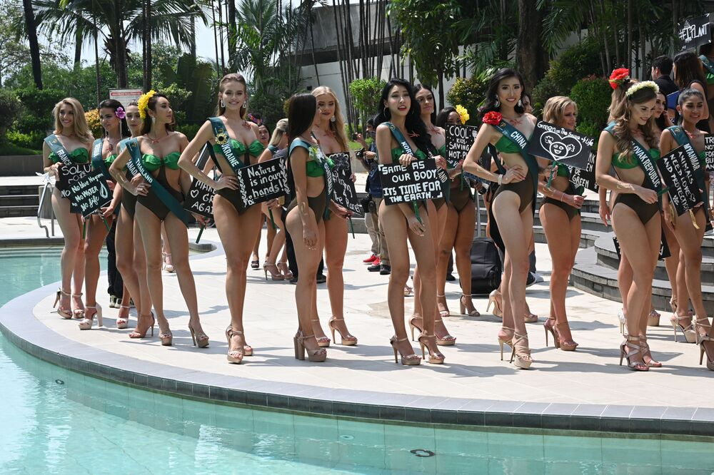 Miss Earth candidates holding placards with environmental slogans pose for photos during a press presentation at a hotel in Manila on October 2, 2019.