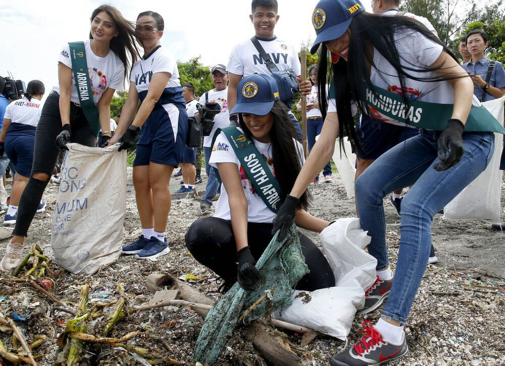 Rita Velasquez, right, of Honduras and Nazia Wadee, center, of South Africa, candidates for the Miss Earth 2019 beauty pageant, join the Philippine Navy as they conduct coastal cleanup, Sept. 30, 2019 in suburban Las Pinas city, south of Manila, Philippines.