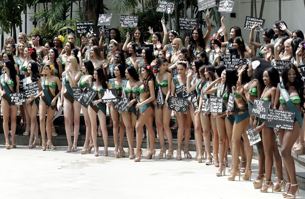 Candidates for the Miss Earth 2019 beauty pageant pose with their messages to save Mother Earth following their media presentation, Wednesday, Oct. 2, 2019 in Manila, Philippines.