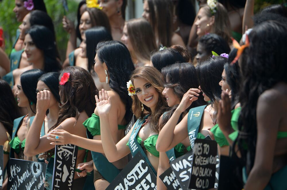 Miss Earth candidate Sonia Hernandez (C) of Spain waves as she poses with other Miss Earth candidates holding placards with environmental slogans during a press presentation at a hotel in Manila on October 2, 2019.