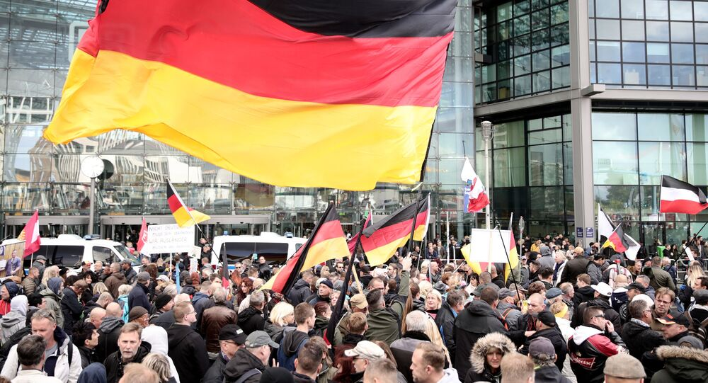 Participants of the right-wing populist demonstration Day of the Nation called by the Alliance We for Germany (Wir fuer Deutschland) gather with German flags at the main station during the German Unification Day in Berlin, Germany, on October 3, 2018.