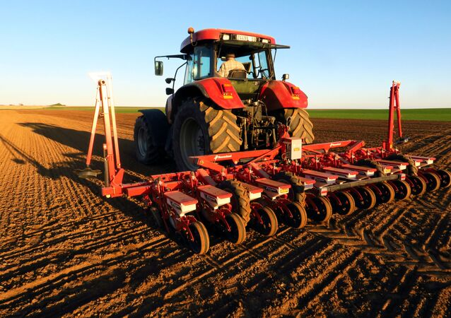 A farmer operates a tractor and a seeder in his field to sow sugar beets in the village of Crevecoeur-sur-Escaut near Cambrai, France, March 24, 2019
