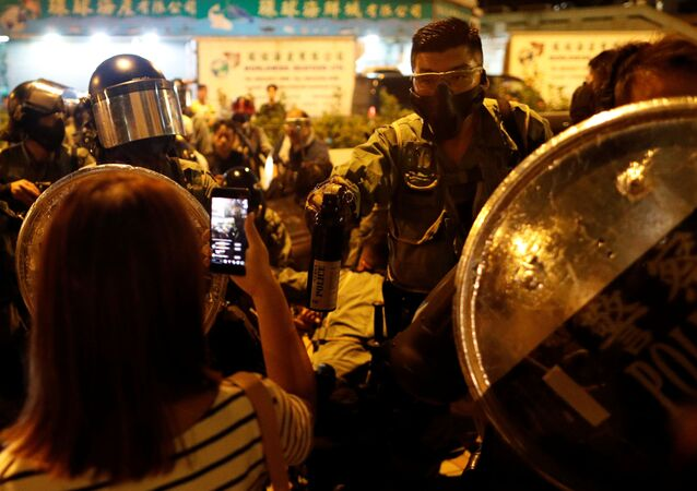 A police officer holds a bottle of pepper spray against protesters at a demonstration at Taikoo station in Hong Kong, China, 3 October 2019.
