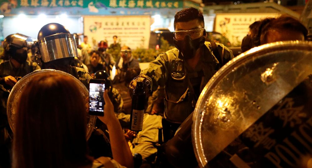 A police officer holds a bottle of peper spray against protesters at a demonstration at Taikoo station in Hong Kong, China October 3, 2019