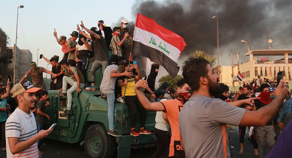 Anti-government protesters take over an armored vehicle before they burn it during a demonstration in Baghdad, Iraq, Thursday, Oct. 3, 2019. Iraqi security forces fired live bullets into the air and used tear gas against a few hundred protesters in central Baghdad on Thursday, hours after a curfew was announced in the Iraqi capital on the heels of two days of deadly violence that gripped the country amid anti-government protests. (AP Photo/Hadi Mizban)