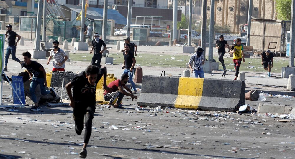 Demonstrators run at a protest during a curfew, three days after the nationwide anti-government protests turned violent, in Baghdad, Iraq October 4, 2019