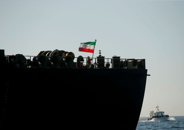A crew member raises the Iranian flag at Iranian oil tanker Adrian Darya 1, formerly named Grace 1, as it sits anchored after the Supreme Court of the British territory lifted its detention order, in the Strait of Gibraltar, Spain, August 18, 2019.