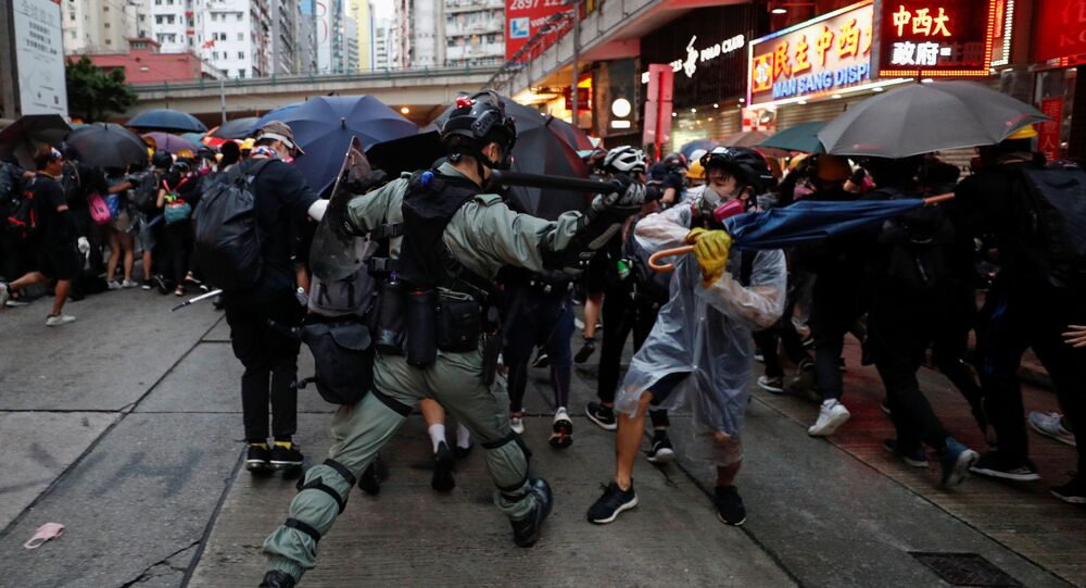 A riot police officer clashes with a protester during an anti-government rally in central Hong Kong, China October 6, 2019