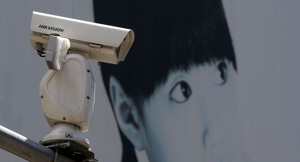 A video surveillance camera made by China's Hikvision is mounted on top of a street near a advertisement poster in Beijing