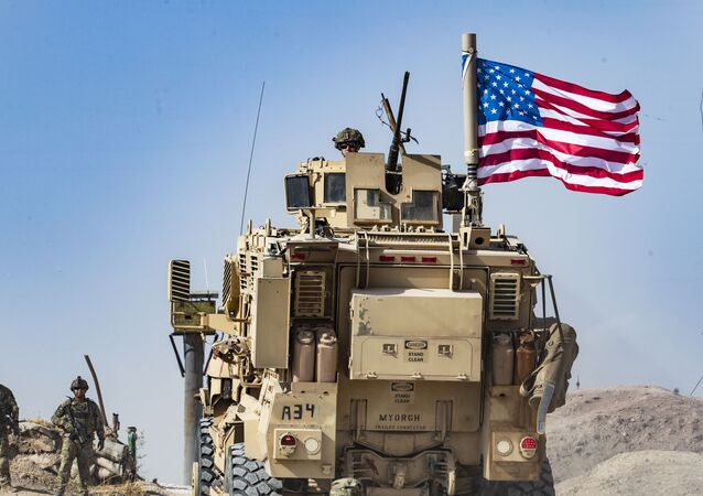 A US soldier sits atop an armoured vehicle