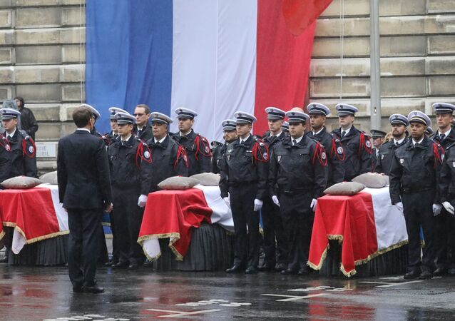 French President Emmanuel Macron stands in front of coffins during a ceremony at The Prefecture de Police de Paris (Paris Police Headquarters) in Paris on October 8, 2019, held to pay respects to the victims of an attack at the prefecture on October 4, 2019.