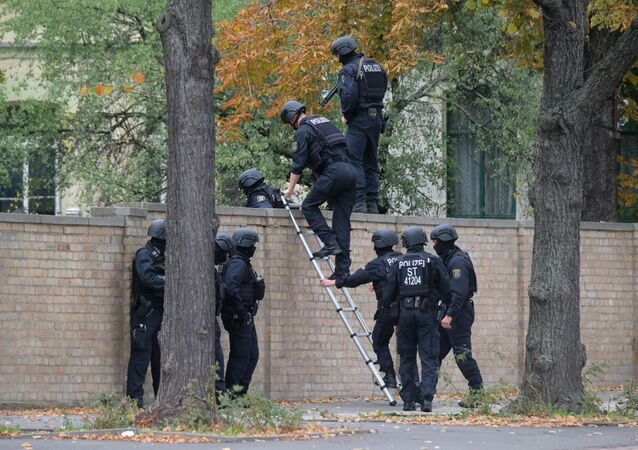 Police officers cross a wall at a crime scene in Halle, Germany, Wednesday, Oct. 9, 2019
