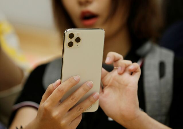 A woman holds an iPhone 11 Pro Max after it went on sale at the Apple Store in Beijing