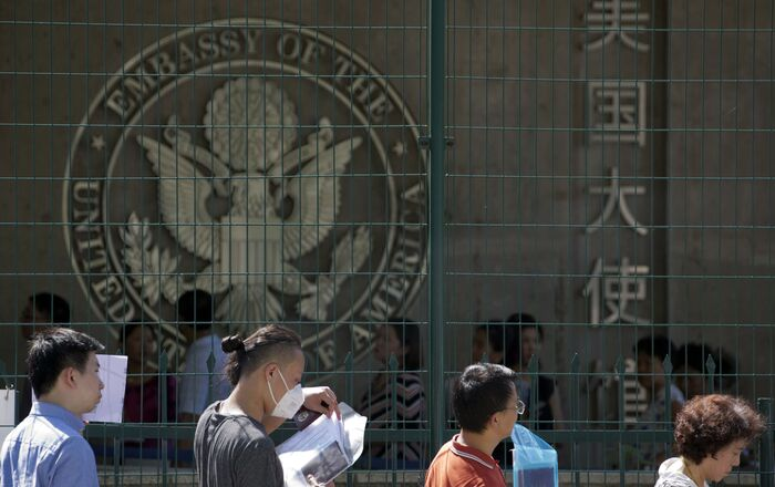 Visa applicants wait to enter the U.S. Embassy in Beijing, China, Thursday, July 26, 2018