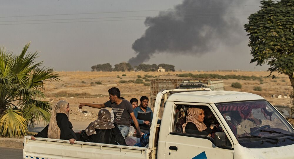 Civilians ride a pickup truck as smoke billows following the Turkish bombardment of the town of Ras al-Ain in northeastern Syria's Hasakeh province, along the Turkish border, on 9 October 2019
