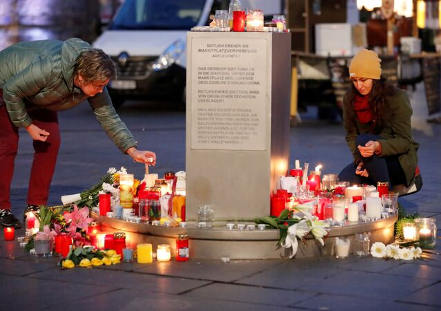 People place candles at central market square in Halle, Germany October 10, 2019, after two people were killed in a shooting