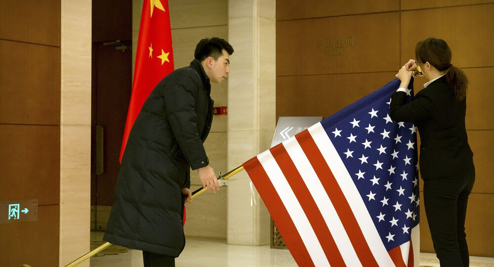 Chinese staffers adjust a U.S. flag before the opening session of trade negotiations between U.S. and Chinese trade representatives at the Diaoyutai State Guesthouse in Beijing, Thursday, Feb. 14, 2019