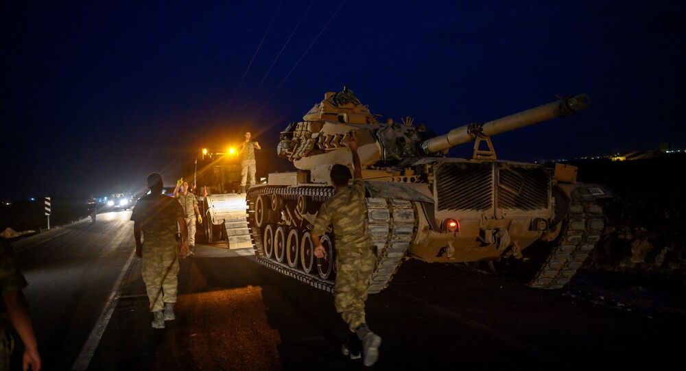 A Turkish army tank drives down from a truck as Turkish armed forces advance towards the border with Syria near Akcakale in Sanliurfa province on 8 October 2019