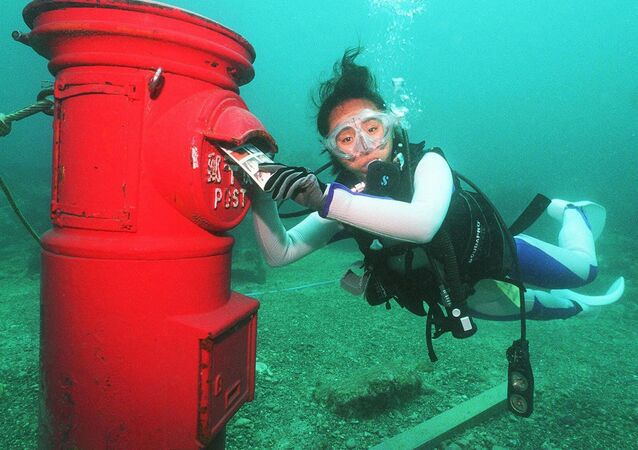 A female skin-diver puts a plastic letter into a post box set up at a depth of 10 meters on bottom of the sea off the coast of Susami, Wakayama Prefecture 07 July 1999.