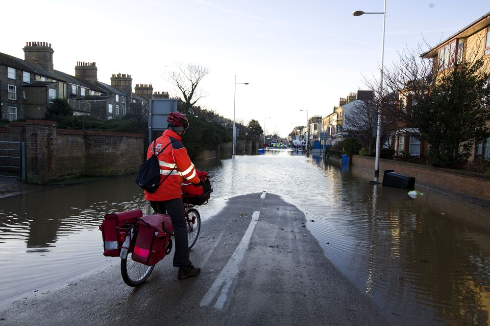A postman stops and looks at a flooded street in Lowestoft, in the east of England, on December 6, 2013 after a tidal surge hit locations along the east coast of Britain.