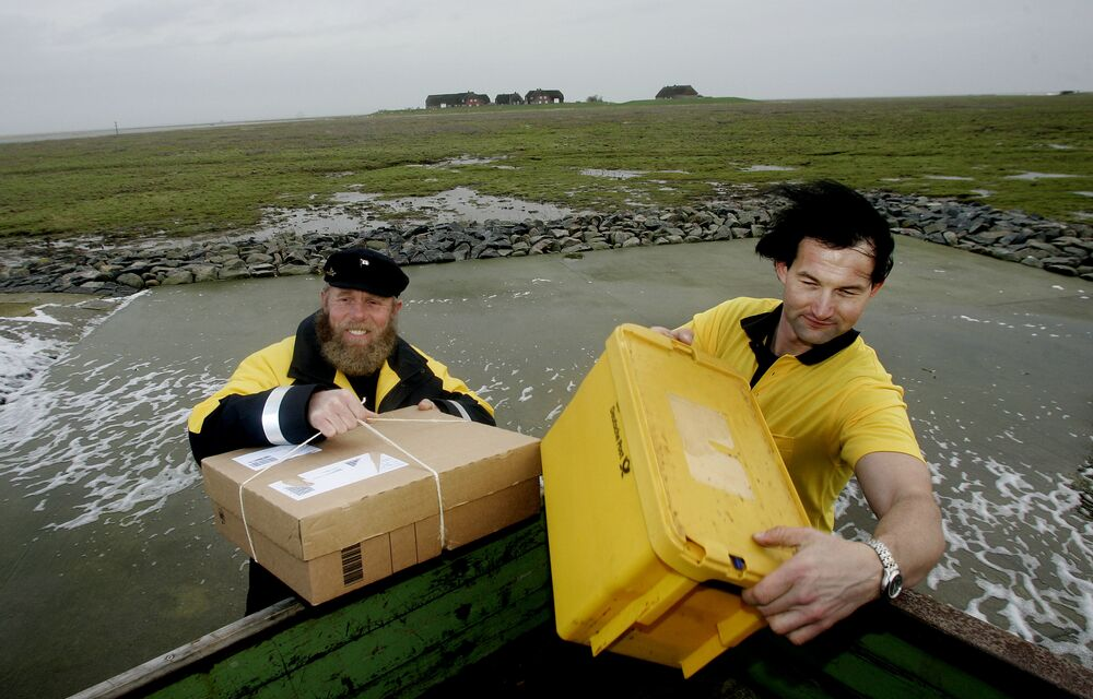 Germany's most northerly post skipper Fiede Nissen, left, and his colleague Andreas Oberauer who is said to be Germany's most northerly postman bring packages and letters to the residents of the tiny island of Groede in the North Sea on Tuesday, Dec.5, 2006.
