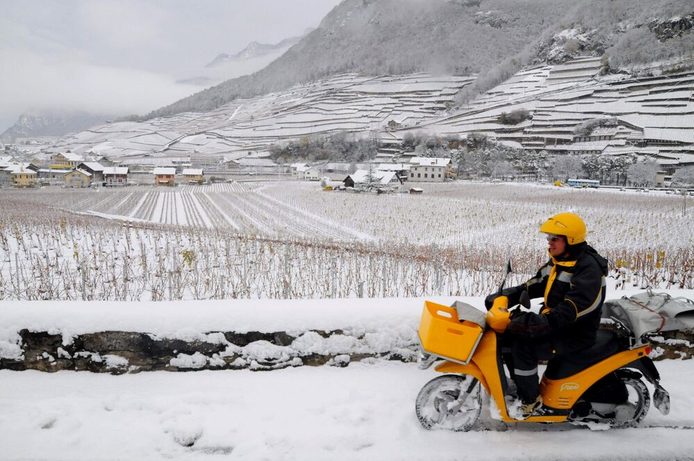 A postman steers his motorcycle through fresh snow in Aigle, Canton of Vaud, western Switzerland, on Monday, Nov. 24, 2008.