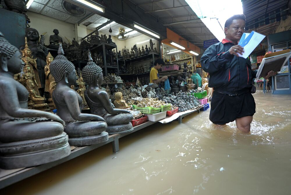 A Thai postman (R) walks through floodwaters at a market in Bangkok on October 27, 2010.
