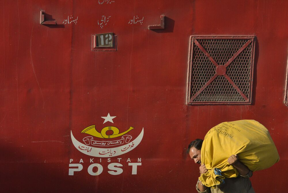 A Pakistani postal worker carries posts at a railway station in Lahore on October 8, 2017, ahead of the World Post Day.