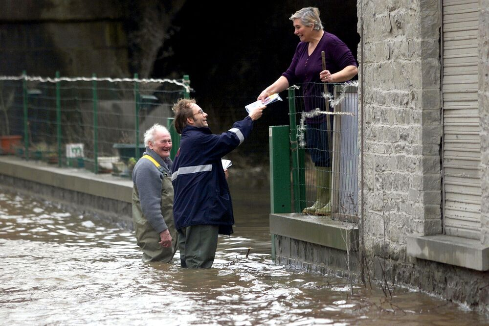 The postman goes on with his round despite floods in the village of Chanxhe, near Liege,  28 January 2002, after heavy rains caused floods in many areas of Belgium.