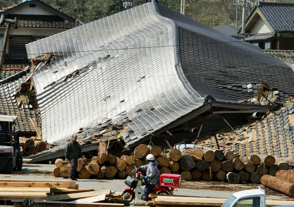 A helmeted postman on a motorcycle rumbles past flattened buildings at Wajima, one of the areas hit hardest in Ishikawa prefecture (state), northern Japan, on Monday March 26, 2007.