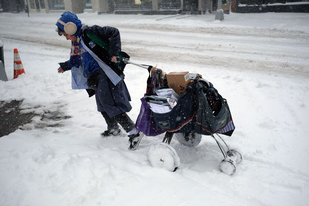 A postwoman drags her mail cart on a snow-covered street during a winter storm in New York on February 9, 2017.