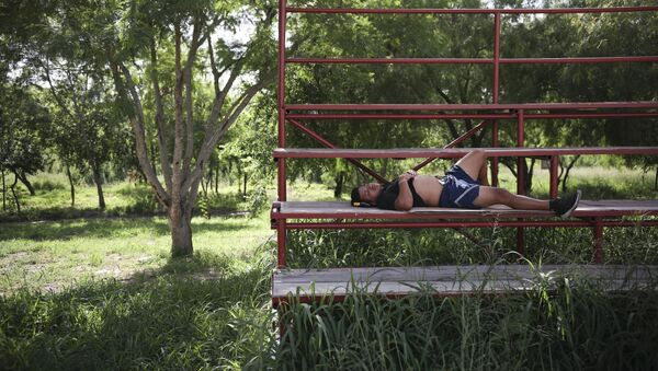 A migrant rests in a park near the entrance to the Puerta Mexico bridge that crosses over the Rio Grande river in Matamoros, Mexico - Sputnik International