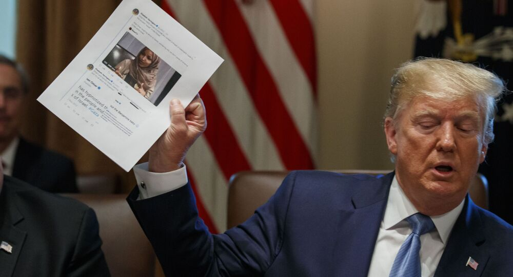 Secretary of State Mike Pompeo, left, looks at a paper held by President Donald Trump about Rep. Ilhan Omar, D-Minn., as Trump speaks during a Cabinet meeting in the Cabinet Room of the White House, Tuesday, July 16, 2019, in Washington