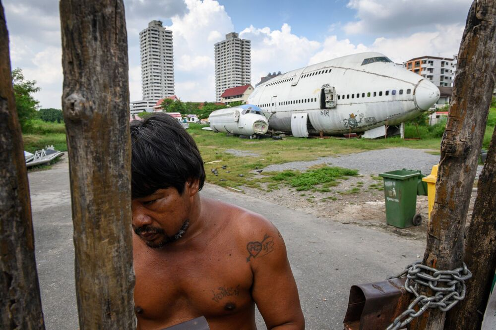 A man charges an entrance fee at a gate in front of abandoned aircraft in the suburbs of Bangkok on October 9, 2019.