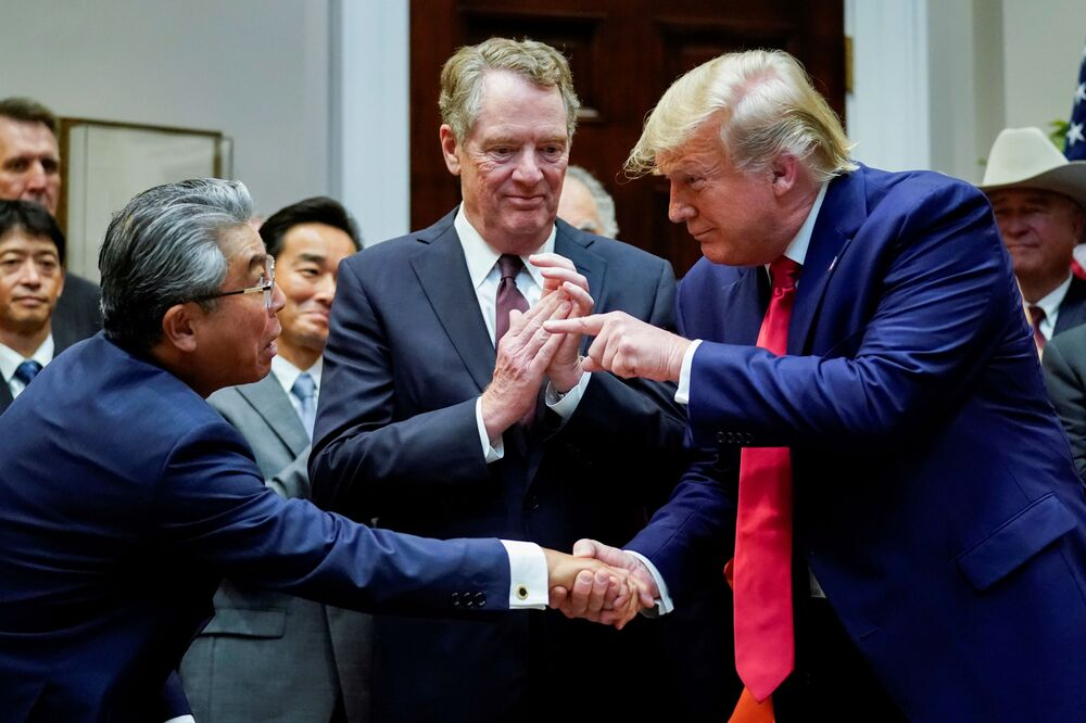 U.S. President Donald Trump shakes hands with Japan's ambassador to the United States Shinsuke Sugiyama in front of U.S. Trade Representative Robert Lighthizer during a formal signing ceremony for the U.S.-Japan Trade Agreement at the White House in Washington, October 7, 2019.