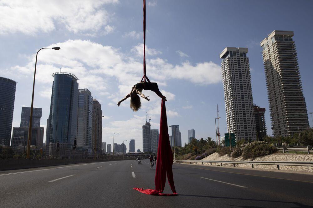 Israeli acrobat Tel Karassin performs on a car-free highway, during the Jewish holiday of Yom Kippur in Tel Aviv, Israel, Wednesday, Oct. 9, 2019.