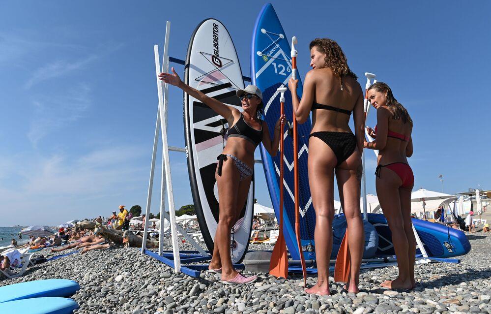 Female holidaymakers are getting ready for a sea surfing in Nizhneimeretinskaya Bukhta, Sochi.