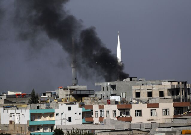 Smoke from a fire caused by an incoming mortar fired from the Syrian side, billows behind a mosque's minarets in Akcakale, Sanliurfa province, southeastern Turkey, smoke billows from targets inside Syria during bombardment by Turkish forces Thursday, Oct. 10, 2019