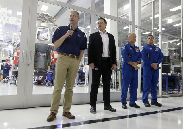 NASA Administrator Jim Bridenstine, left, talks with SpaceX chief engineer Elon Musk, second from left, and NASA astronauts crew Doug Hurley and Bob Behnken, right, in front of the Crew Dragon spacecraft, about the progress to fly astronauts to and from the International Space Station, from American soil, as part of the agency's commercial crew program at SpaceX headquarters, in Hawthorne, Calif., Thursday, Oct. 10, 2019