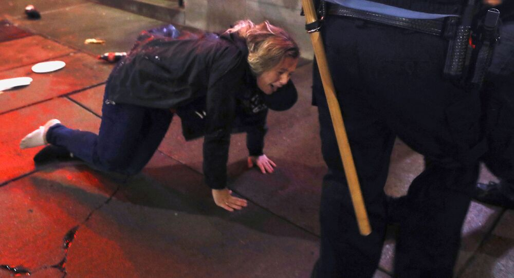 A woman is knocked to the ground after a rally by U.S. President Donald Trump in Minneapolis, Minnesota, U.S. October 10, 2019