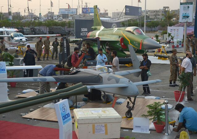 Pakistani officials prepare a locally-manufactured GIDS Shahpar unmanned aerial vehicle for display as a PAC JF-17 Thunder multirole combat aircraft, jointly developed by China and Pakistan, is seen in background at right during preparations for the International Defence Exhibition and seminar (IDEAS) in Karachi on November 29, 2014