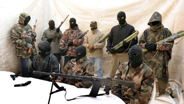 Hooded and clad in military fatigues, armed with guns, rocket launchers, members of a commando claiming to belong to the National Liberation Front of Corsica answer media questions at a press conference held near Ajaccio on May,2010 - Sputnik International